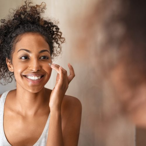 Young,Black,Woman,Applying,Moisturising,Cream,On,Cheeck,While,Standing