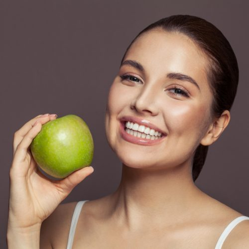 Lovely,Woman,Holding,Green,Apple,And,Smiling,On,Brown,Background