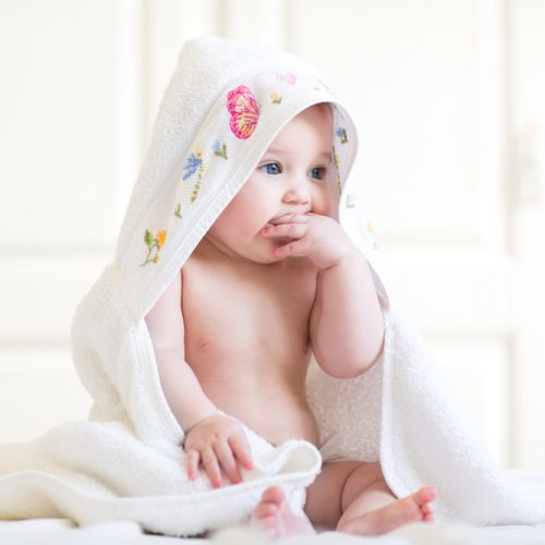 Adorable,Baby,Girl,Sitting,Under,A,Hooded,Towel,After,Bath
